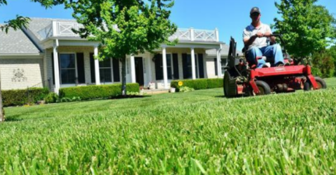 A man on a ride on mower is mowing a lawn in front of a house on a sunny and clear day.