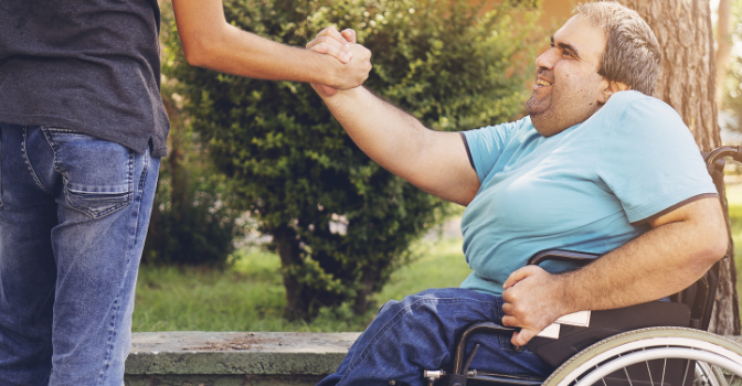 A man in a wheelchair is smiling while reach up to grasp hands with a friend who is off camera.
