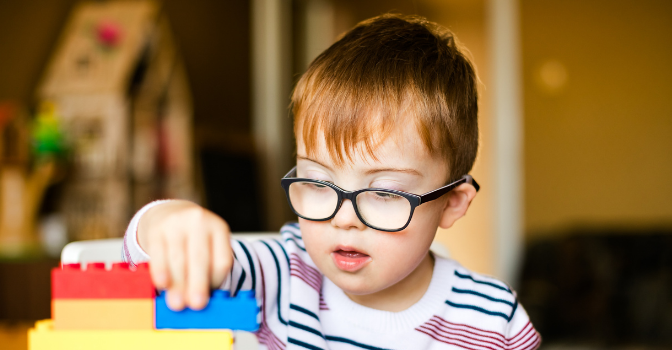 A young boy in glasses stacks building blocks.