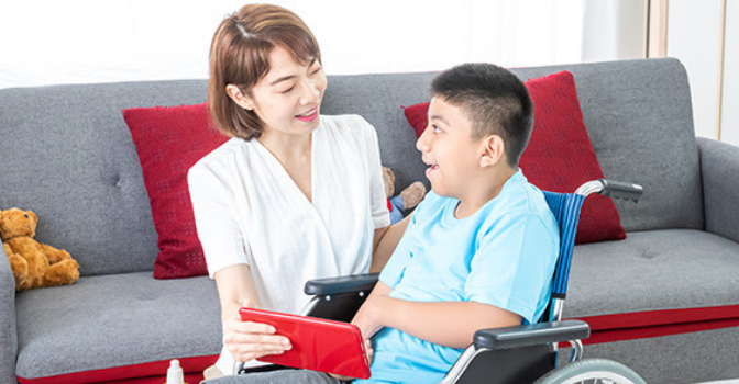 A boy in a wheelchair is looking up and smiling at a woman holding a tablet in front of them both.