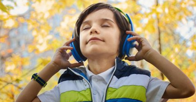 Young boy holding headphones over his ears with his eyes closed.