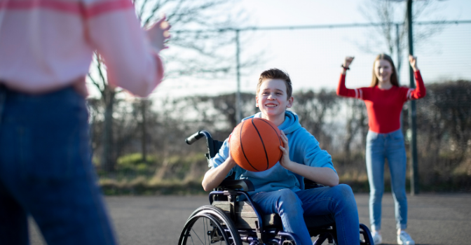 A boy in a wheelchair is playing basketball with 2 friends and it about to pass the ball to a person that is only half in the frame.