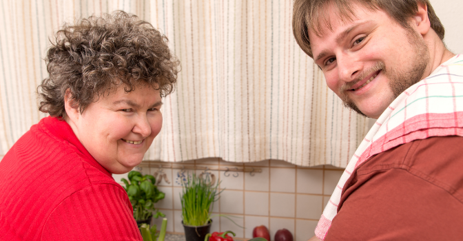 A woman and her carer are smiling at a camera while standing in a kitchen.