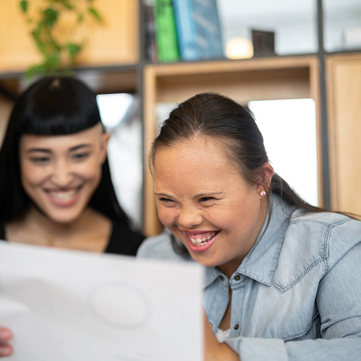 Young girl looking at a document with a colleague
