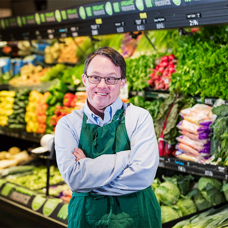 Man, in uniform with arms crossed, in fresh food section of supermarket.