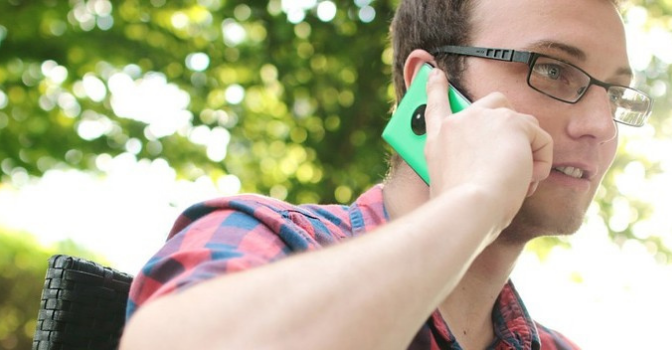 A man with glasses is holding a green phone to his ear.