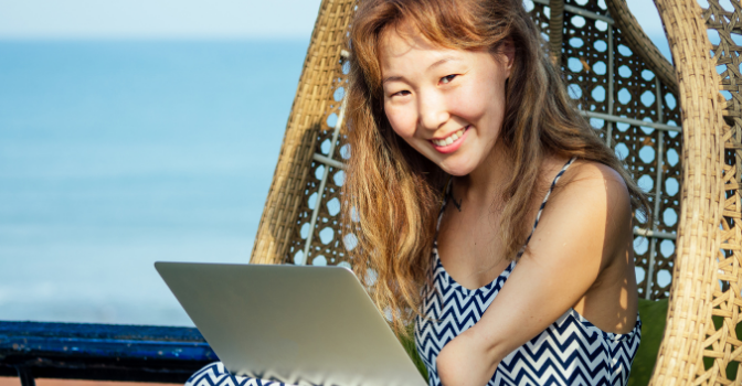 A lady with a partial limb sits on a rattan egg chair while on her laptop smiling at the camera.