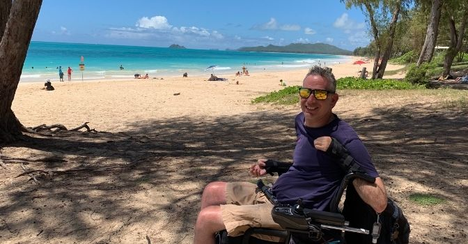 Lindsay is on the beach in his wheelchair smiling. It is a beautiful sunny day in the background.