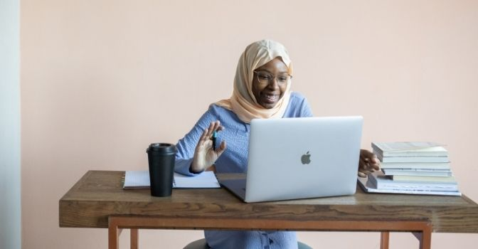 A woman is at her desk with a laptop waving and smiling to someone on screen.