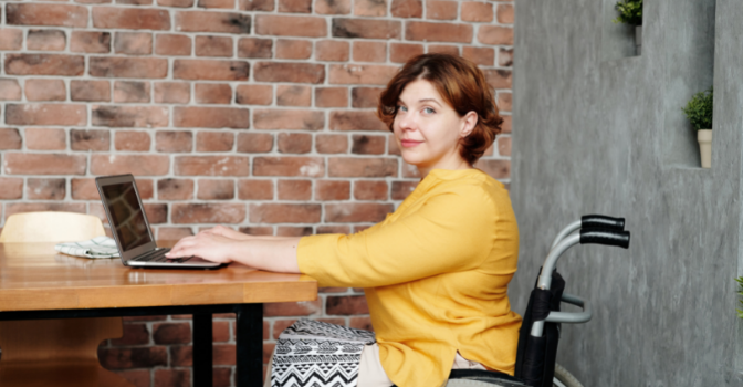 A lady in a wheelchair in a yellow top sits at a table with her laptop. Her head is turned and she is smiling at the camera.