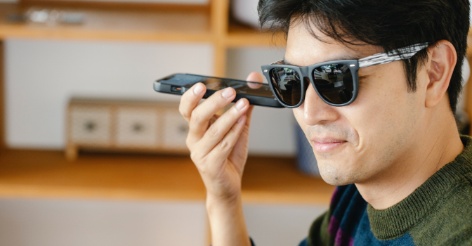 A vision impaired man is sittin wearing sunglasses and holding his phone to his ear.