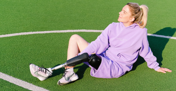 A woman para athlete sits in the sun in purple workout clothing on a green sports field.