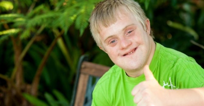 A boy with Down Syndrome in a green shirt is looking at the camera smiling with a thumbs up.