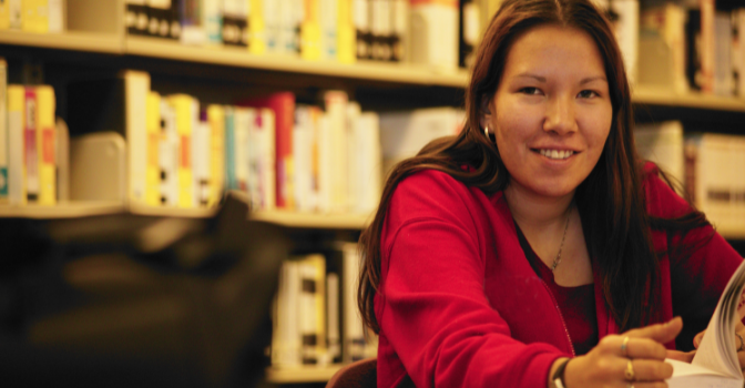 A student sits at a desk in a library while looking and smiling at the camera.