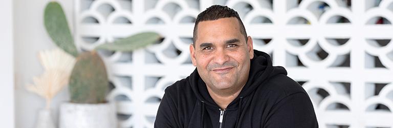Man, smiling, wearing black hoodie sitting in waiting area